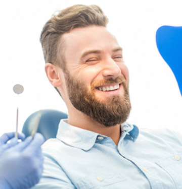 Man smiling at himself in the mirror in dentist's chair