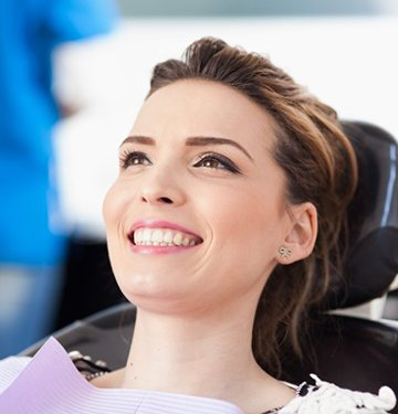 woman smiling in chair of emergency dentist in West Bloomfield