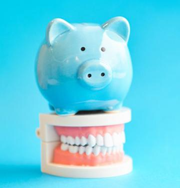 blue piggy bank sitting on top of dentures against blue background