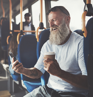 man laughing at his phone on a bus