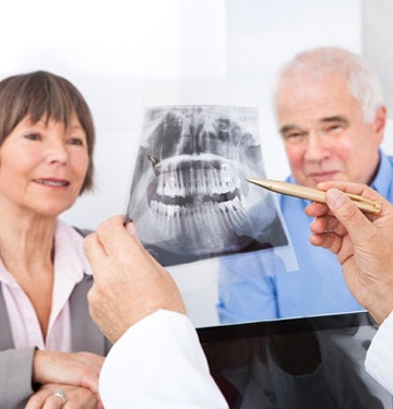 A dentist showing an older couple an X-ray.