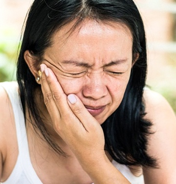 woman with toothache who needs emergency dentist in West Bloomfield