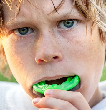 little boy inserting light green mouthguard