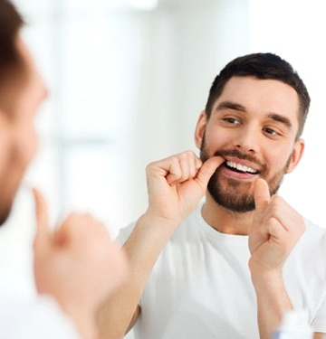 bearded man in white t-shirt flossing