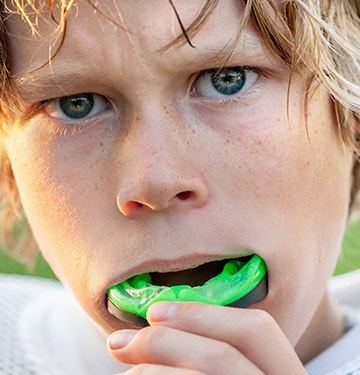 Teen boy placing green sports mouthguard