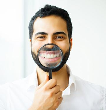 man using magnifying glass to show off his veneers in West Bloomfield