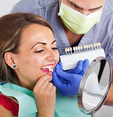 woman in red shirt trying on veneers in dental chair