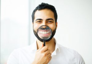 man holding magnifying glass to his smile with porcelain veneers in West Bloomfield