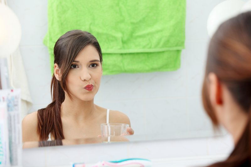 Woman looking in mirror while rinsing with mouthwash